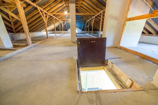 Чердак здания с деревянными балками конструкции крыши и двери пожарного выхода в пол. Premium Фотографии