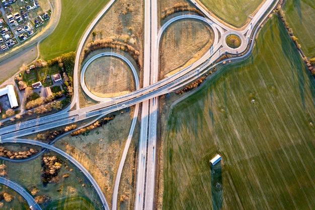 現代の高速道路の交差点、春の緑のフィールドの背景に家の屋根の空中のトップビュー。ドローン写真。 Premium写真