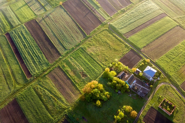 晴れた春の日に田園風景の平面図。ファームコテージ、家、緑と黒のフィールド上の納屋は、スペースの背景をコピーします。ドローン写真。 Premium写真