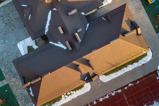 複雑な構成構造を持つ茶色の鉄片瓦屋根を上から見た航空写真。抽象的な背景、幾何学模様。 Premium写真