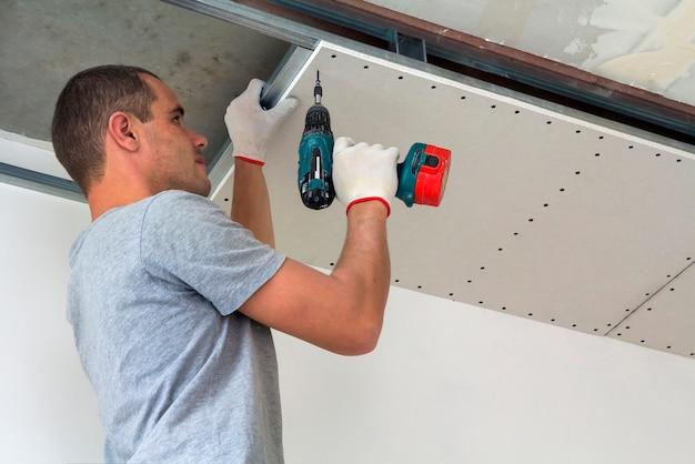 建設作業員は、乾式壁で吊り天井を組み立て、ドライバーで乾式壁を天井の金属フレームに固定します。 Premium写真