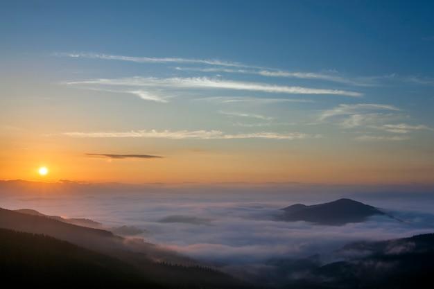 カルパティア山脈、ウクライナの美しい霧の風景日の出。 Premium写真