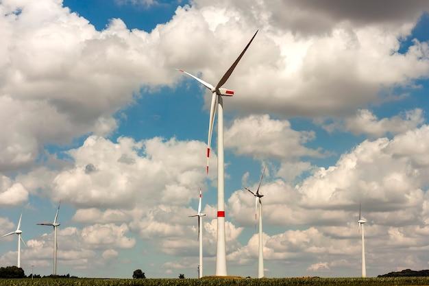 フィールド上の風車。風力発電機は、夏の風景を発電するタービンです。グリーン再生可能エネルギー。 Premium写真
