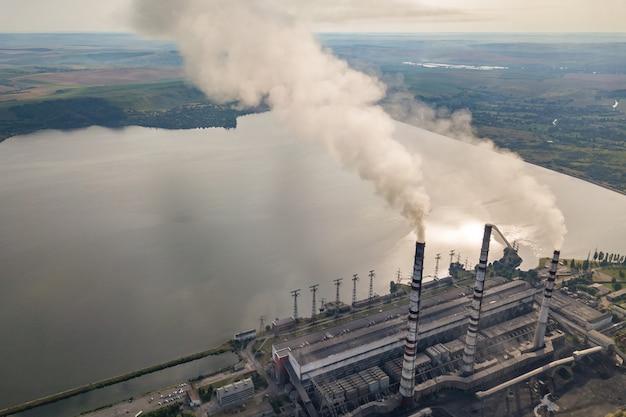 石炭発電所からの灰色の煙と高い煙突パイプの空撮。化石燃料による電気の生産。 Premium写真