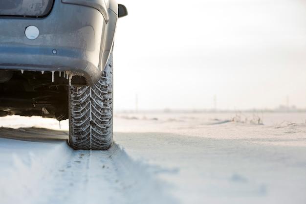 深い雪の中で車の車輪のゴム製タイヤのクローズアップ。輸送および安全コンセプト。 Premium写真