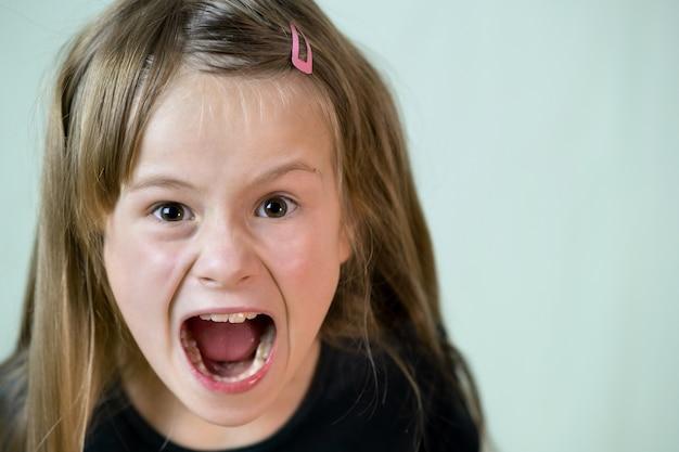 Крупным планом портрет злой кричать ребенка девушка, агрессивно глядя в камеру. Premium Фотографии