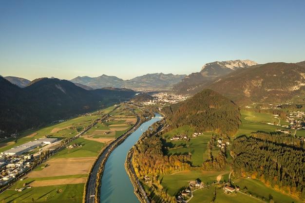 アルプスの山々の大きな川の近くの高速移動トラフィックと高速道路州間道路の空撮 Premium写真
