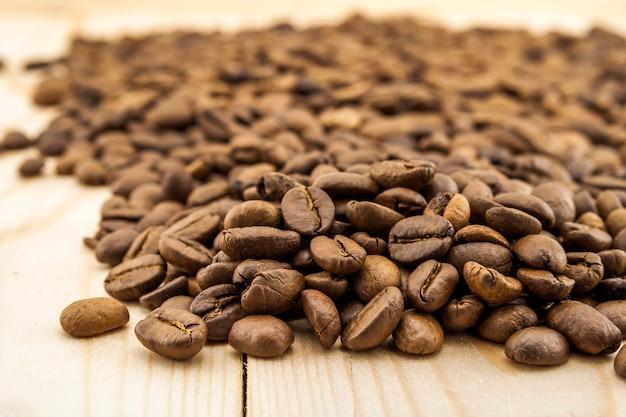 黄色のテクスチャ木製ボードの背景に茶色のコーヒー豆をクローズアップ。 Premium写真