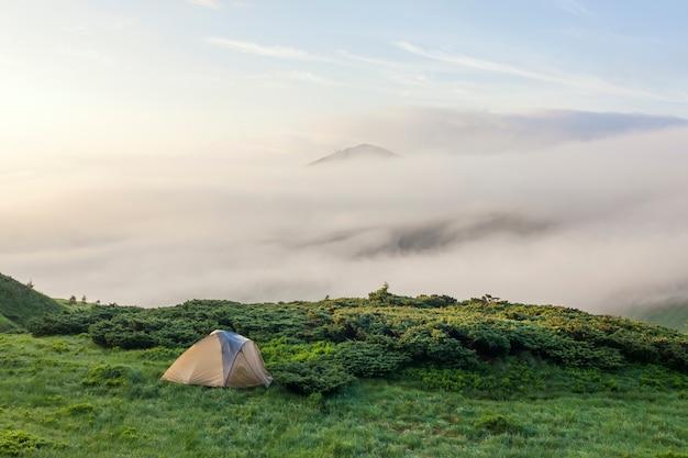冷たい霧の夏の朝とカルパティア山脈の観光ハイカーテントのパノラマ Premium写真