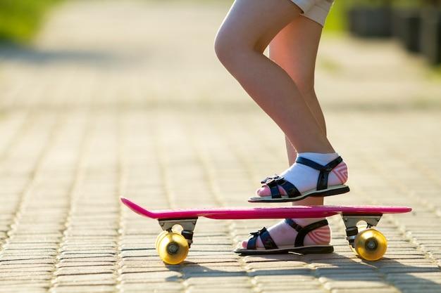 Детские стройные ножки в белых носках и черных сандалиях на пластиковом розовом скейтборде Premium Фотографии