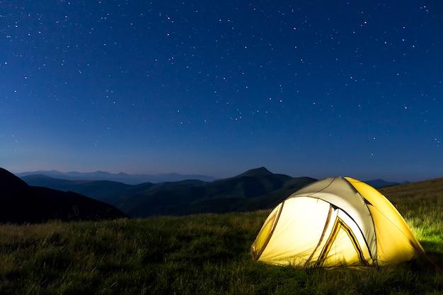 Туристическая палатка туристов в горах ночью со звездами на небе Premium Фотографии