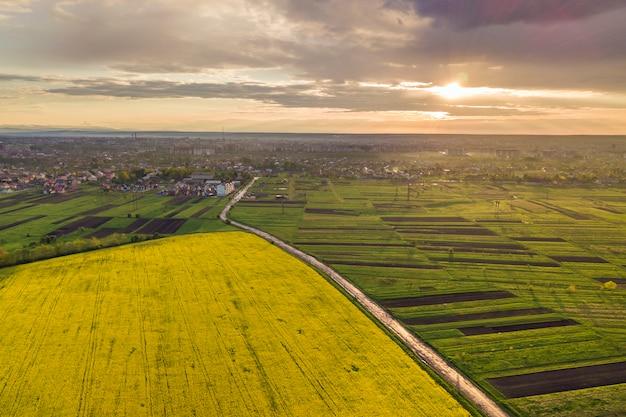 春または夏の日の田園風景。緑、耕した、咲く畑、家の屋根、道路の空撮。 Premium写真