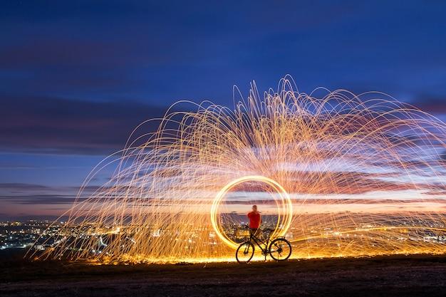 夜の街でスチールウールを紡ぐことで、熱く輝く花火のシャワー。 Premium写真