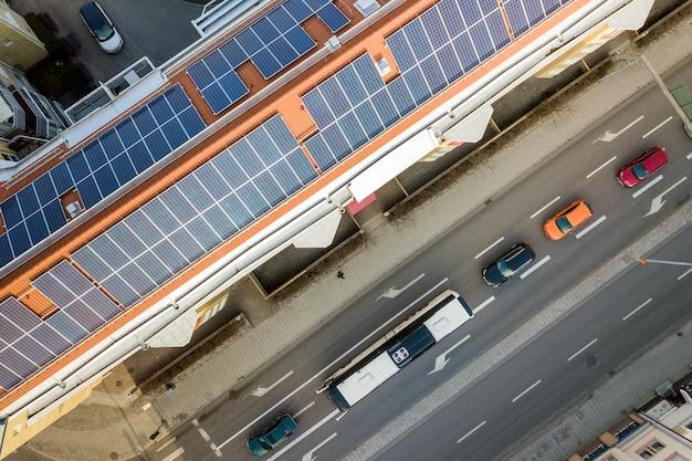 晴れた日に高いアパートの建物の屋根の上の青い太陽光発電パネルシステムの平面図。 Premium写真