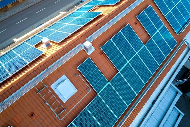 アパートの建物の屋根の上の青い太陽光発電パネルシステムの平面図。再生可能なグリーンエネルギー生産。 Premium写真