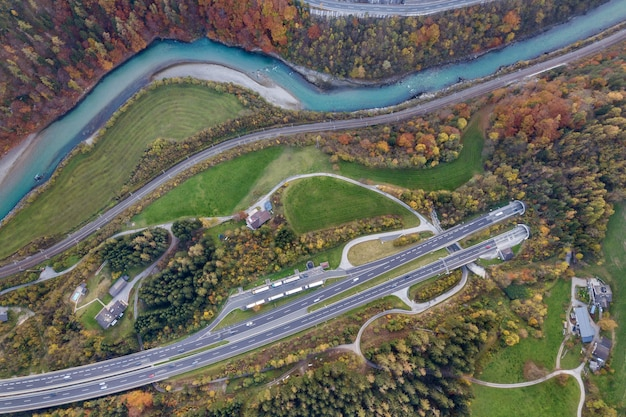 Верхний вид с воздуха рассвета скоростной дороги скоростного шоссе идя вне от подземного тоннеля между желтыми лесными деревьями осени и голубым рекой. Premium Фотографии