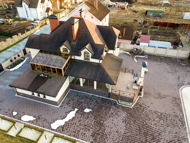 晴れた日にフェンスで囲まれた大きな庭に鉄片屋根の新しい住宅コテージの空中のトップビュー。 Premium写真