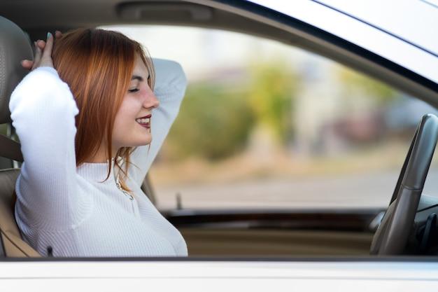 若い赤毛の女性ドライバーが幸せそうに笑って車で休んでいるシートベルトで固定されています。 Premium写真
