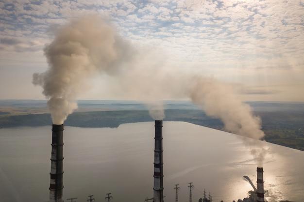 Вид с воздуха труб высокой дымовой трубы с серым дымом от электростанции угля. производство электроэнергии с использованием ископаемого топлива. Premium Фотографии