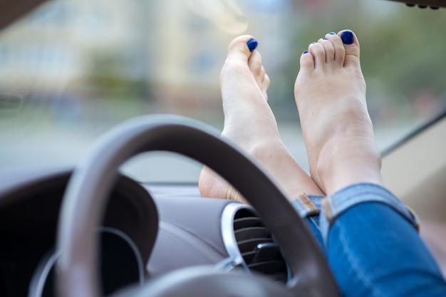 Закройте вверх ног водителя женщины отдыхая на приборной панели автомобиля. Premium Фотографии