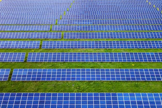 緑の芝生で再生可能なクリーンエネルギーを生産する太陽光発電パネルシステムの大分野。 Premium写真