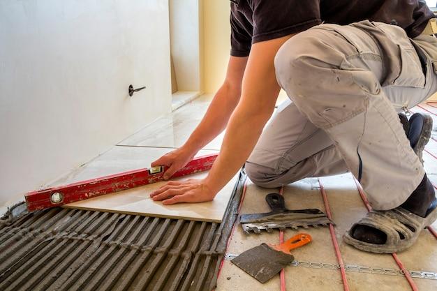 Юный рабочий плиточник укладывает керамическую плитку с помощью рычага на цементный пол с системой обогрева красным электрическим кабелем Premium Фотографии