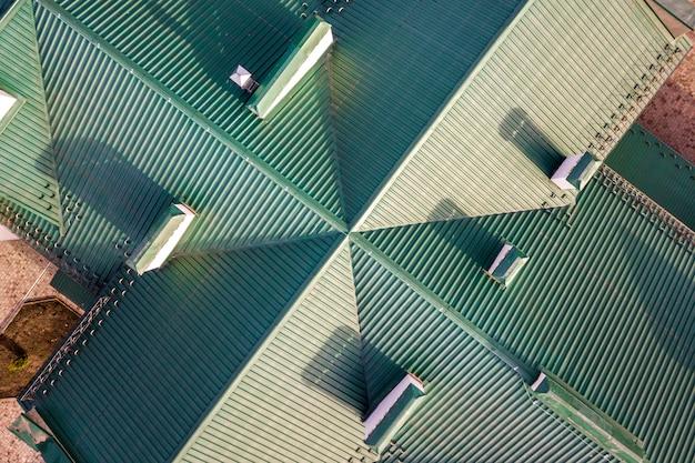 緑の鉄片瓦屋根の建物を上から見た航空写真。 Premium写真