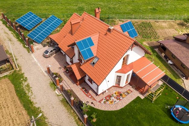 Воздушный взгляд сверху нового современного жилого коттеджа дома с голубой сияющей солнечной системой фотоэлектрических панелей на крыше. концепция производства экологически чистой зеленой энергии. Premium Фотографии