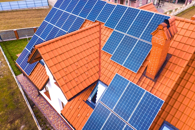 屋根の上の青い光沢のある太陽光発電システムと新しいモダンな住宅コテージの空中のトップビュー。再生可能な生態学的なグリーンエネルギー生産の概念。 Premium写真