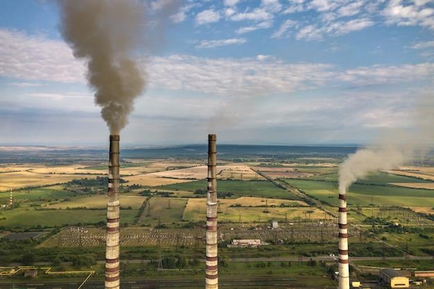 石炭発電所からの灰色の煙で高い煙突のパイプの空撮。化石燃料による発電。 Premium写真