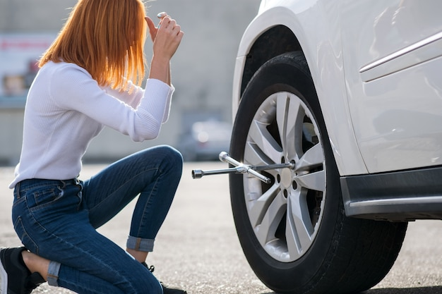 壊れた車のホイールを変更するレンチを持つ若い女性。 Premium写真
