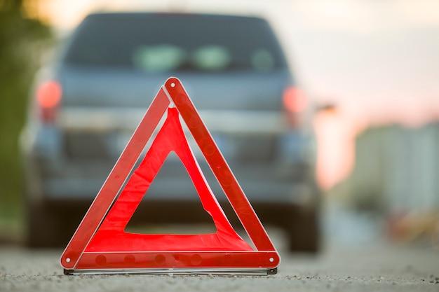 赤い緊急三角形の一時停止の標識と壊れた車が街の通り。 Premium写真