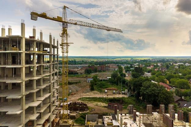 タワーリフトクレーンと都市で建設中の高層マンションのコンクリートフレームの空撮。都市開発と不動産成長のコンセプト。 Premium写真