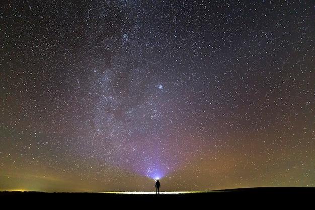 美しい暗い夏の星空の下で芝生のフィールドに頭の懐中電灯を持つ男の黒いシルエット。 Premium写真
