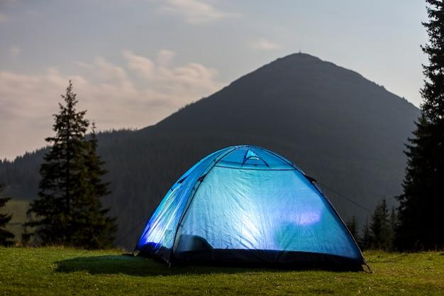 観光ハイカーは、晴れた朝の空の下で背の高い松の木の間でクリア緑の草が茂った森の明るい青いテント。 Premium写真