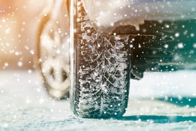 冬の深い雪の中で車の車輪のゴム製タイヤのクローズアップ。輸送と安全。 Premium写真