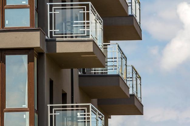 バルコニーと青い空に輝く窓のあるアパートの建物の壁のクローズアップの詳細。 Premium写真