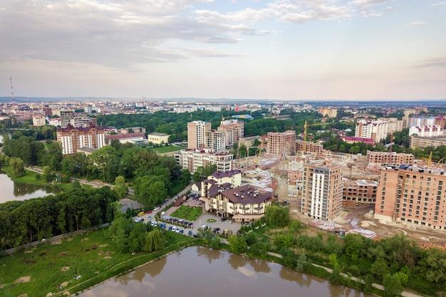 Взгляд сверху городского развивающего ландшафта города с высокорослыми жилыми домами и домами пригорода. дрон аэрофотосъемки. Premium Фотографии