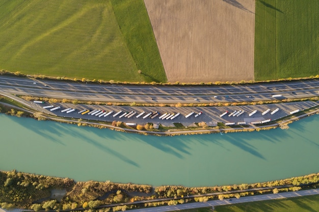 高速で移動する交通のある高速道路の州間道路と駐車したトラックの駐車場を上から見下ろした図。 Premium写真