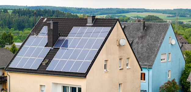 Возобновляемые экологически чистые энергосберегающие эффективные солнечные батареи на крыше загородного дома. Premium Фотографии