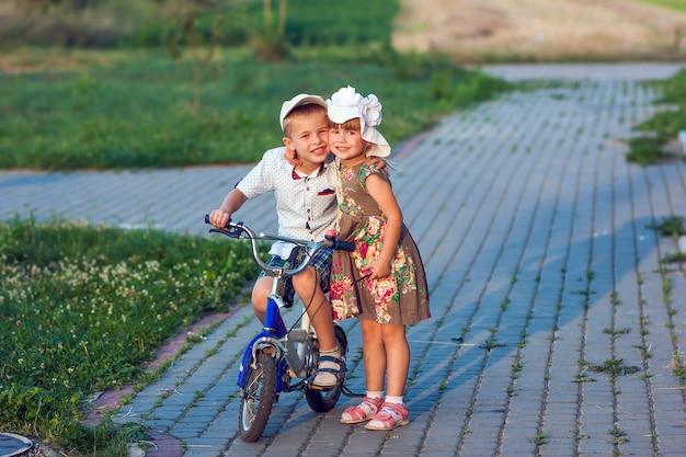Мальчик и девочка на велосипеде, играя на улице в солнечный летний день Premium Фотографии
