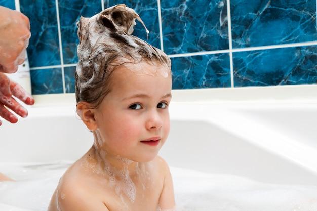 浴室で小さな乙女チックな頭を洗うママの手。 Premium写真