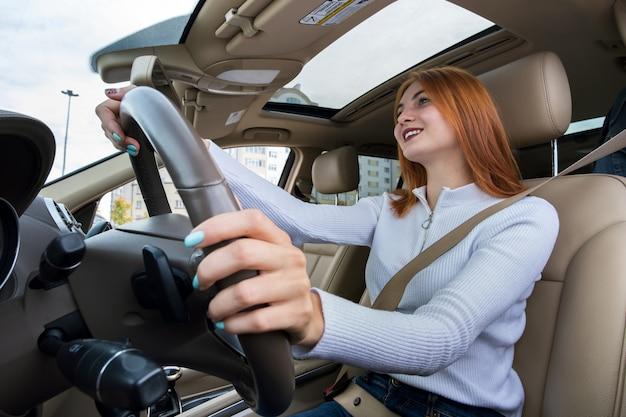 幸せそうに笑って車を運転するシートベルトで固定された若い赤毛の女性ドライバーの広角ビュー。 Premium写真