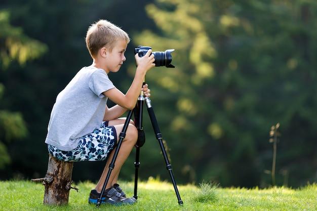 Молодой белокурый мальчик ребенка сидя на пне дерева на травянистой расчистке фотографируя с камерой треноги. Premium Фотографии