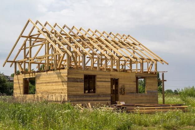 緑のフィールドで建設中の自然生態木材の新しいコテージ。木製の壁と急な屋根フレーム。プロパティ、投資、専門的な建物と再建のコンセプト。 Premium写真
