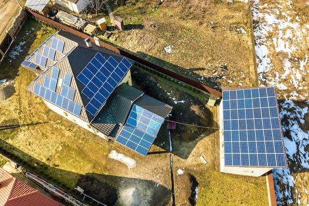 屋根の上の青い光沢のある太陽光発電太陽光発電パネルシステムと新しいモダンな住宅コテージの空中の平面図。再生可能な生態学的なグリーンエネルギー生産の概念。 Premium写真