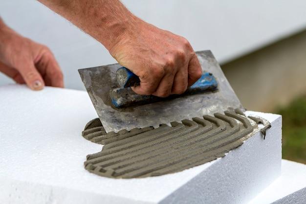 Рабочая рука с помощью шпателя наносит клей на пенополиуретановый лист для утепления дома. Premium Фотографии