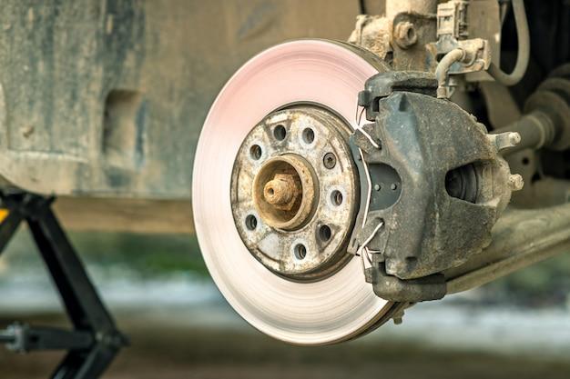 Крупный план тормозного диска корабля с тормозным суппортом для ремонта по мере замены новой шины. ремонт тормозов в гараже. Premium Фотографии