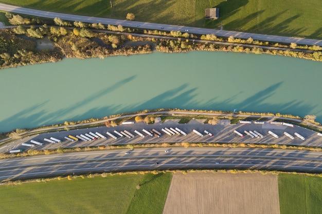 Сверху вниз вид шоссе шоссе межгосударственной дороги с быстрым движением трафика и стоянка с припаркованными грузовиками. Premium Фотографии