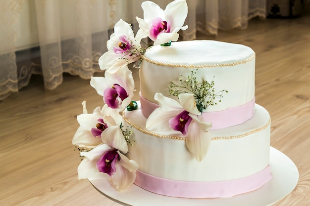 花と美しいウェディングケーキ、ぼやけたケーキのクローズアップ Premium写真